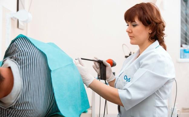 Врач проктолог проводит диагностику геморроя аноскопию